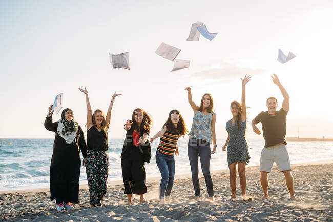Six beautiful women and a man, all throwing papers into the air on the beach, with the sun behind them — Stock Photo