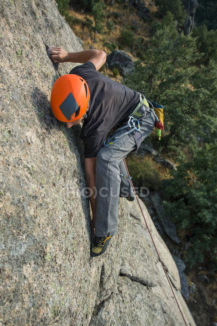 From above man climbing a rock in nature with climbing equipment — Stockfoto