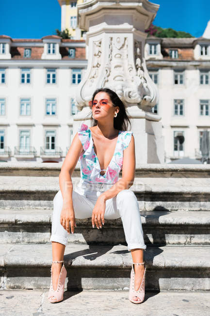 Relaxed beautiful woman in trendy outfit sitting on stone staircase on scenic street — Foto stock