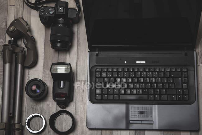 Dall'alto set di attrezzature fotografiche professionali disposte vicino al laptop su una superficie di legno — Foto stock