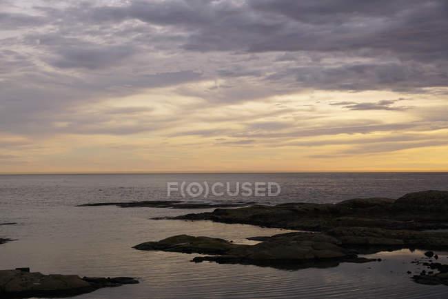 Forma abundante de enormes acantilados rocosos sobre la costa tranquila helada contra el cielo escénico nocturno. - foto de stock