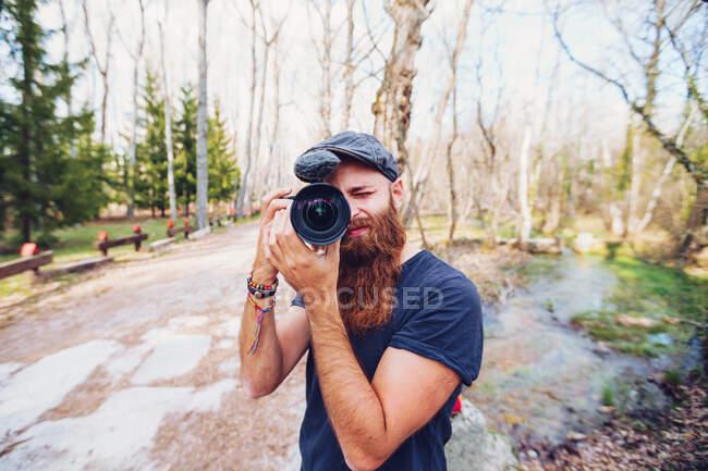 Сучасний бородатий рудий чоловік у шапці фотографується з камерою, стоячи на дорозі в оточенні безлисті дерева в барвистих лісах у сонячний осінній день. — стокове фото