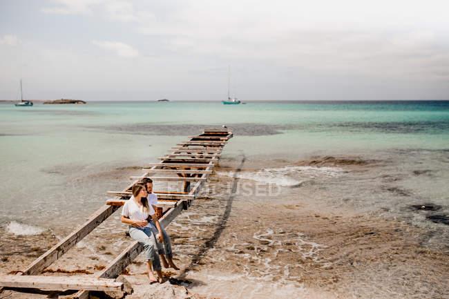 Gli amanti felici seduti sul molo distrutto sulla riva del mare — Foto stock