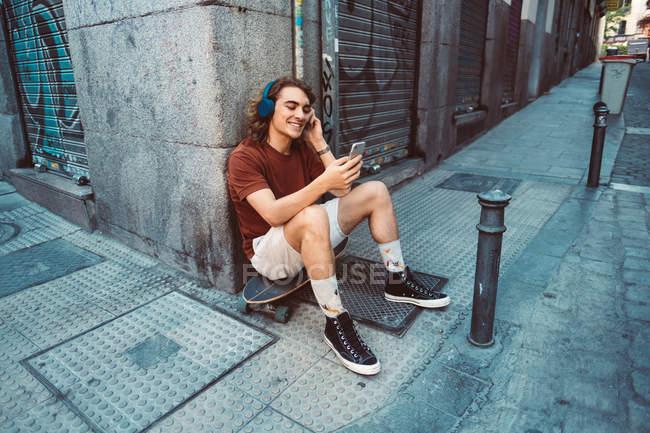 Unbekümmerter Mann mit Kopfhörern surft auf dem Longboard und baut auf der Straße — Stockfoto