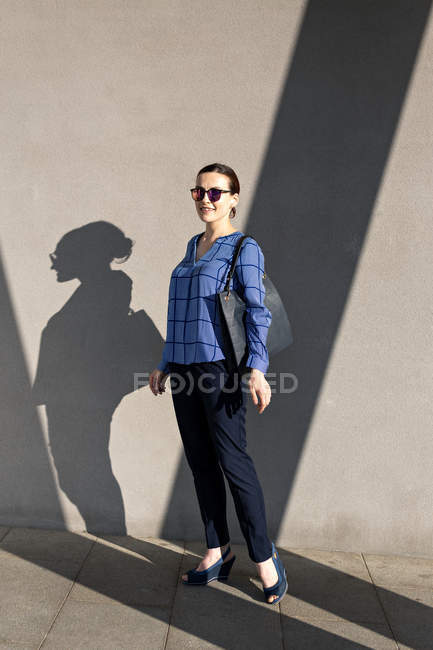 Manager in sunglasses and elegant outfit smiling and looking at camera while standing on street — Fotografia de Stock