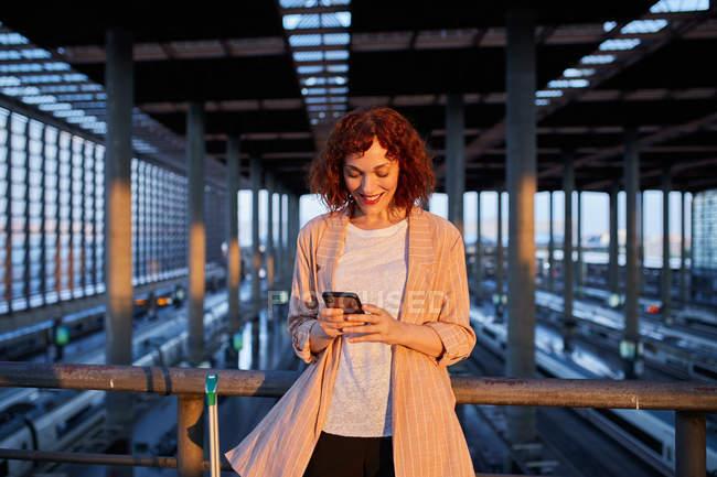 Sorridente giovane donna che naviga telefono alla stazione — Foto stock