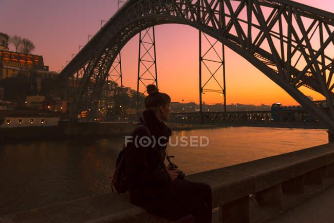 Vista laterale del turista donna con macchina fotografica guardando dall'altra parte mentre seduto sul bordo del terrapieno della città vicino al ponte durante il tramonto a Oporto, Portogallo — Foto stock
