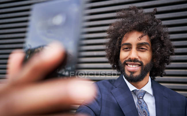 Bearded African American man with curly hair smiling while taking selfie next to striped wall — Stock Photo