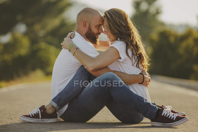 Side view of happy couple in matching casual clothes embracing and looking at each other while sitting on countryside road — Stock Photo