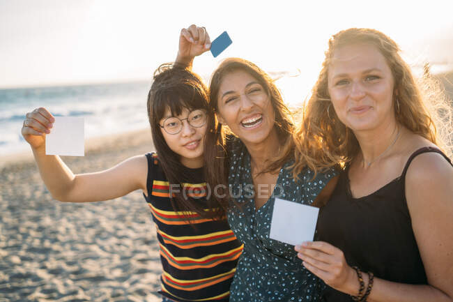 Colorful portrait of three beautiful and smiling women hugged showing cards looking at camera with the sun behind them — Stock Photo