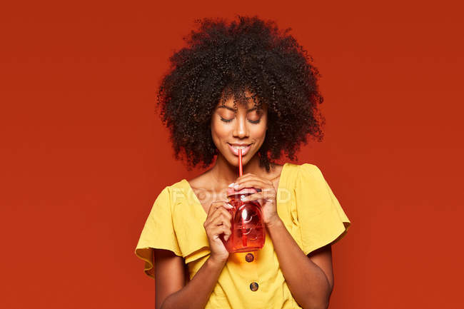 Dreamy African American woman with curly hair holding red jar with straw and enjoying beverage on red background — Stock Photo