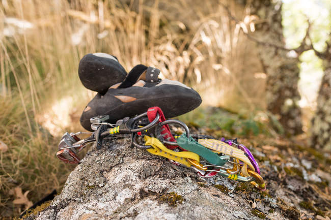 Climbing equipment, ropes, climbing shoes, carabines, ready to be used next to the mountain hillside - foto de stock