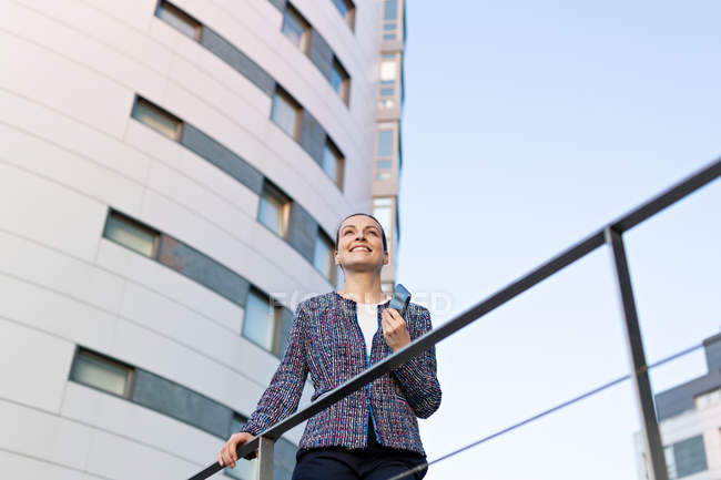 Low angle of serious female manager in elegant outfit leaning on railing and looking away — Fotografia de Stock