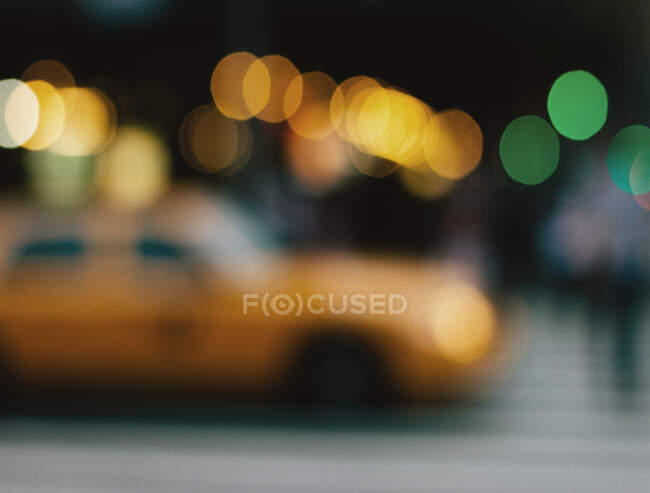 Затьмарений міський пейзаж жовтого таксі, що проходить повз Нью-Йорк, повний яскравих бокейських вогнів — стокове фото