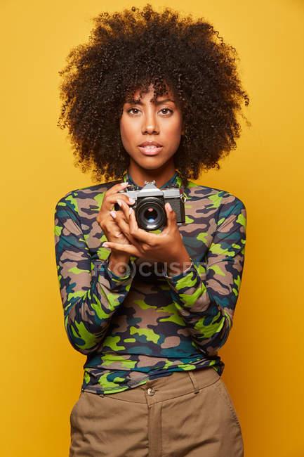 Photographe professionnelle, coiffeuse afro-africaine tenant un appareil photo sur fond jaune — Photo de stock