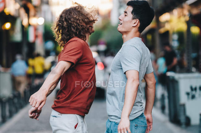 Side view of excited multiracial men jumping together and slamming chests on city street — Stock Photo
