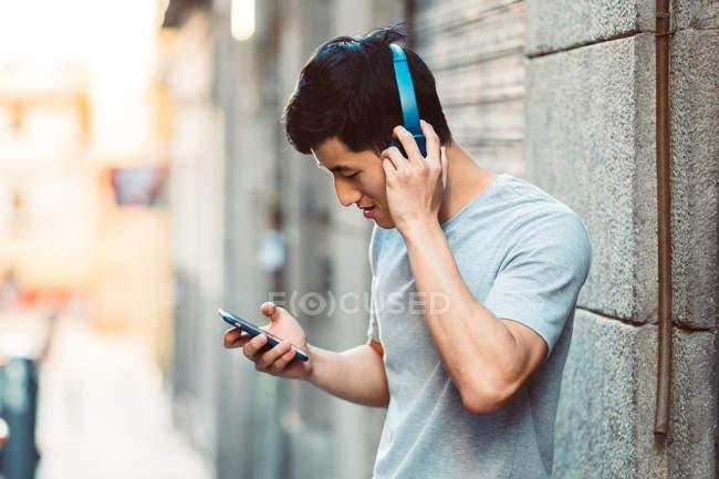 Joyful casual asiático homem em fones de ouvido usando smartphone enquanto em pé na ensolarada rua da cidade — Fotografia de Stock