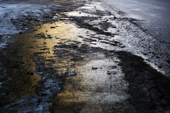 Wheel trace on asphalt road with muddy melted snow in twilight - foto de stock