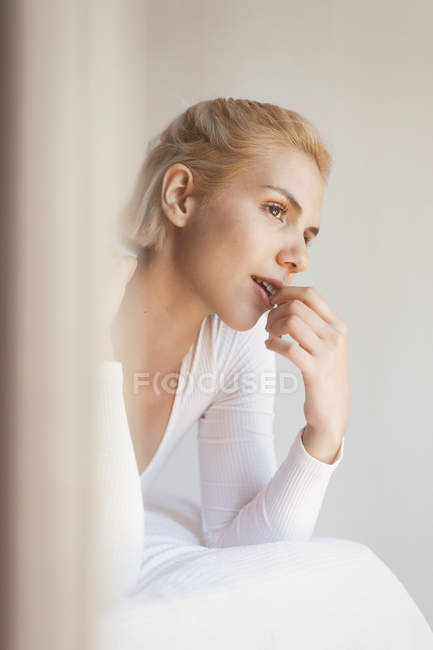 Young woman with blond hair and in bodysuit looking away at home — Stock Photo