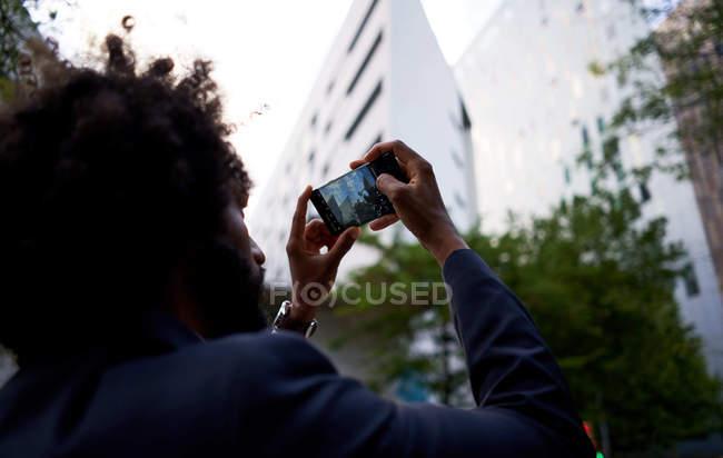 Visão traseira do empresário masculino afro-americano na moda em roupas formais tirando fotos de edifícios residenciais — Fotografia de Stock