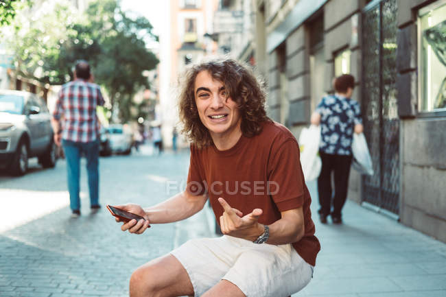 Cheerful casual surprised man making faces while on smartphone while sitting on baluster on city street — стокове фото