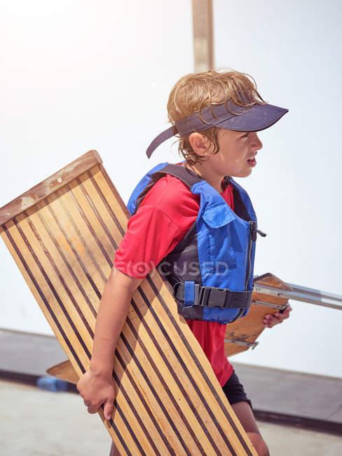 Вид сбоку на мальчика в спасательной куртке, держащего деревянный стенд и идущего после купания — стоковое фото