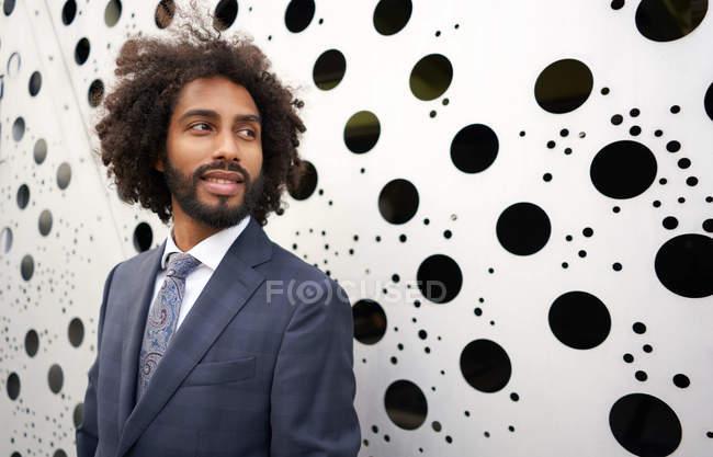 Felice imprenditore afro-americano con i capelli ricci in piedi vicino facciata edificio creativo e sorridente, mentre guardando altrove — Foto stock