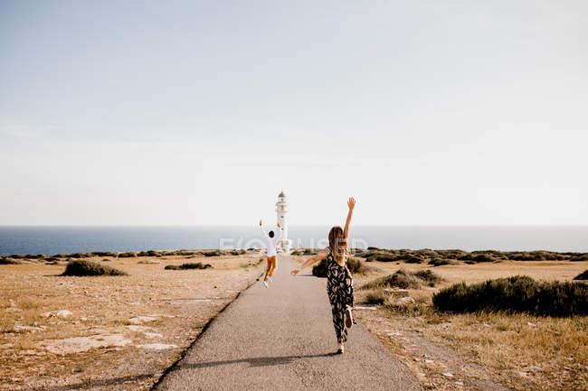 Amanti felici che saltano con le braccia alzate sul sentiero verso il faro — Foto stock