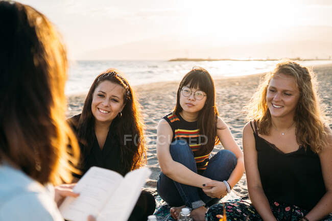 Three beautiful women paying attention to their friend who reads them a book on the beach, blonde girl, brown hair girl and Asian girl with the sun behind her - Concept of vacation — Stock Photo