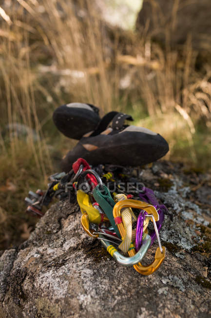 Climbing equipment, ropes, climbing shoes, ready to be used next to the mountain hillside - foto de stock