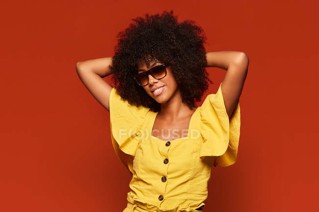 Modern young black woman with Afro hairstyle holding hands behind head while smiling at camera on bright red background — Stock Photo