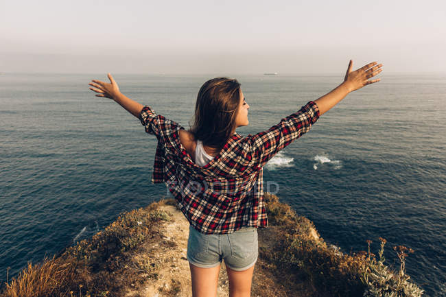 Back view of woman raising arms while standing on stony cliff against endless sea and grey sky — Stock Photo