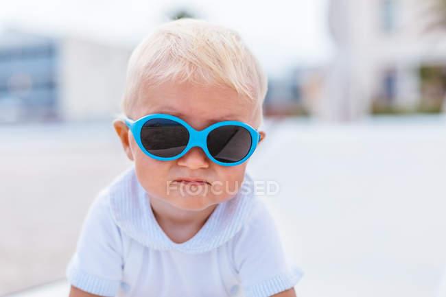 Porträt eines blonden Babys mit Sonnenbrille am Strand — Stockfoto