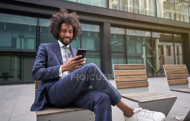 Радісний афроамериканець сидить надворі і обмінюється повідомленнями. — стокове фото