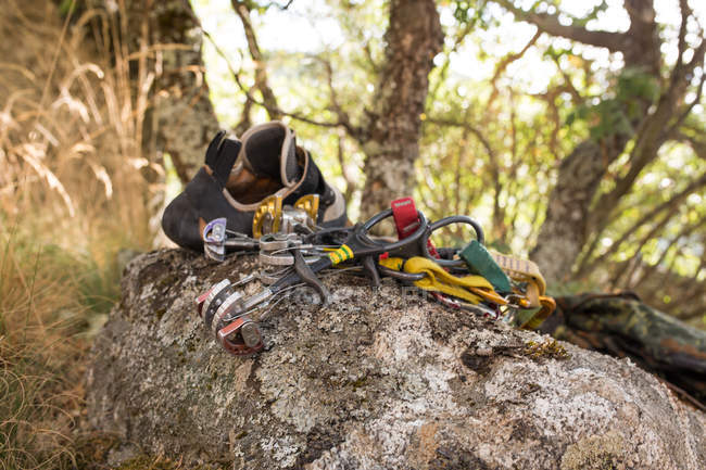 Climbing equipment, ropes, climbing shoes, carabines, ready to be used next to the mountain hillside — Stock Photo