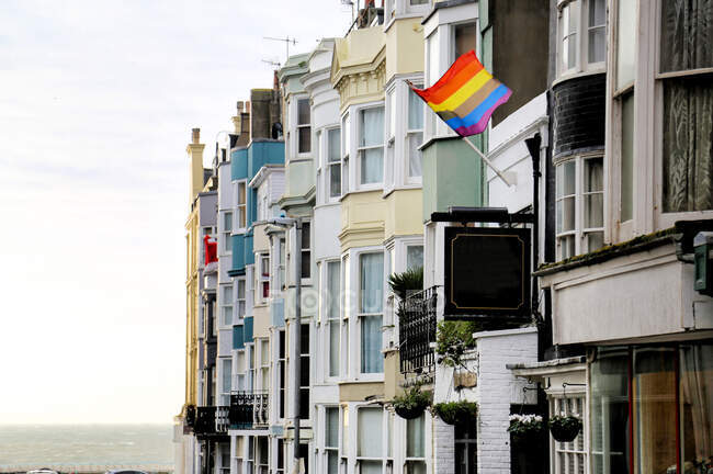 Bright rainbow flag symbolizing LGBT movement and hanging on facade of old residential building on street of Brighton near sea — Stock Photo
