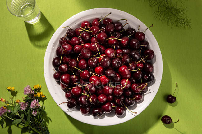 Top view of fresh sweet cherries in bowl on green tablecloth — Stock Photo