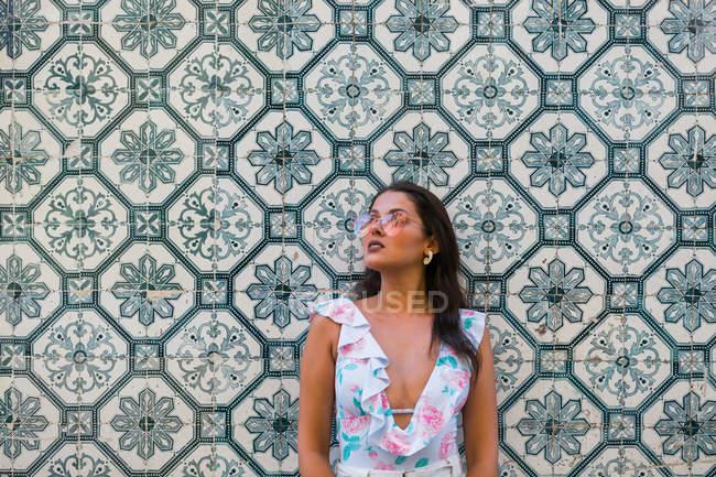 Мирна чарівна жінка в модному одязі і блискучі сонцезахисні окуляри стоять поруч покритий плиткою екзотичної стіни на мальовничій вулиці. — стокове фото