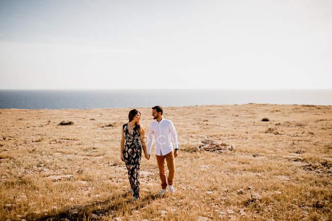 Peaceful lovers bonding on empty coastline — Stock Photo