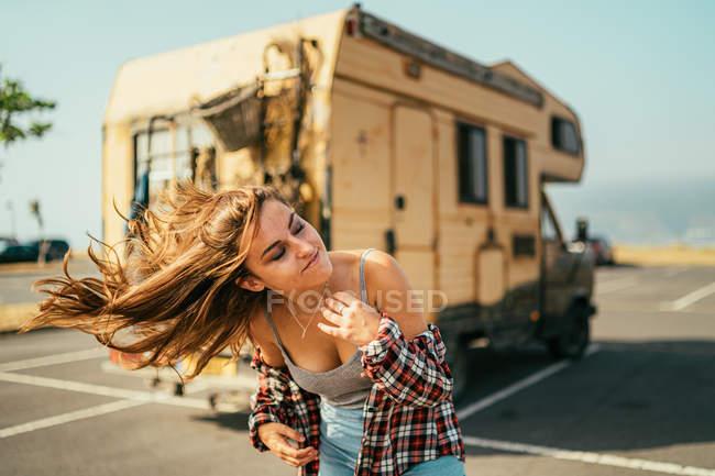 Femme élégante en chemise de plaid et en shorts en denim chemise contre le vent sur le terrain de stationnement sur fond de voiture de camping — Photo de stock