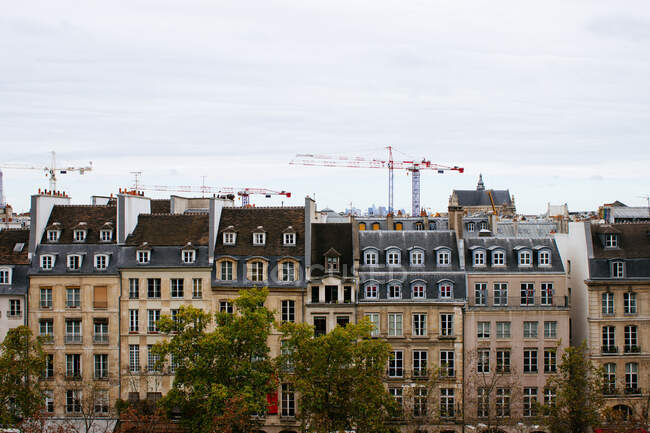 View of city dense district with simple European buildings against tower cranes under gray sky — Stock Photo