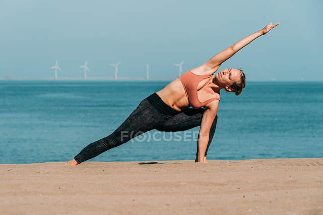 Femme concentrée étirant et faisant du yoga sur une plage ensoleillée — Photo de stock