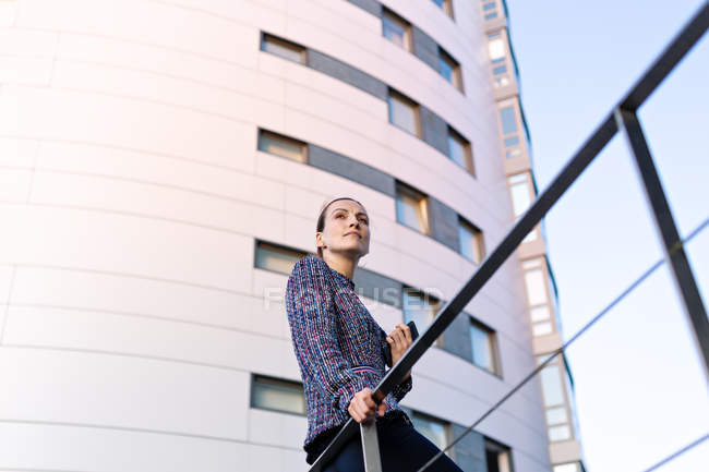 Low angle of serious female manager in elegant outfit leaning on railing and looking away — Stock Photo