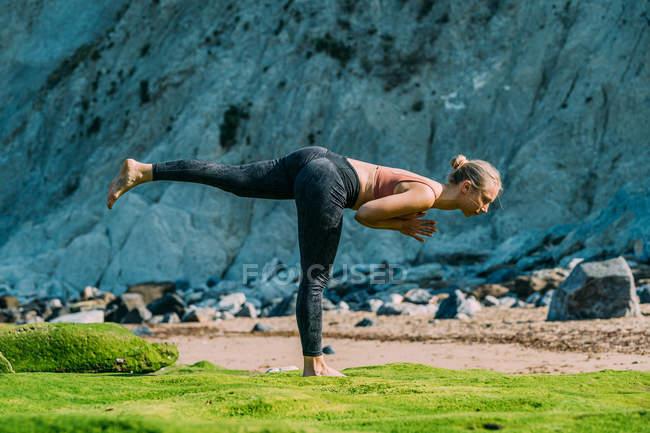 Seitenansicht einer fitten, ruhigen Frau, die Asana mit erhobenem Bein macht, während sie auf buntem Boden neben einer Klippe steht — Stockfoto