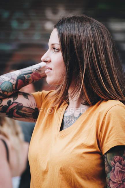 Позитивная современная женщина в футболке улыбается, стоя возле городского дома на городской улице — стоковое фото