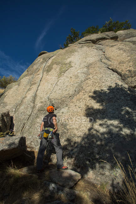 Rock climber with orange helmet is staring at the top of the mountain he is going to climb - foto de stock