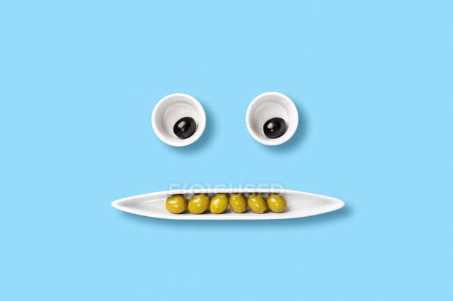 Aceitunas en bandeja formando una cara. Composición divertida de la comida. Arte pop - foto de stock