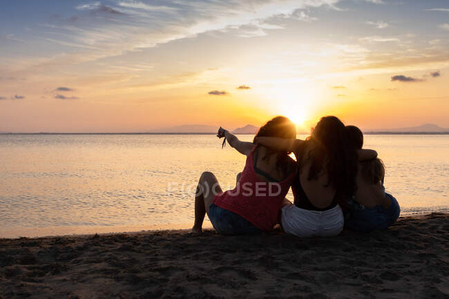 Compañeros pacíficos abrazándose en la orilla del mar - foto de stock