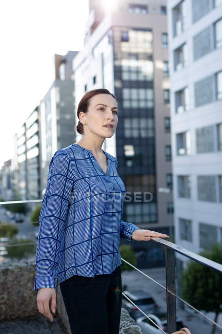Side view of pretty female manager in checkered shirt smiling and looking away — Stock Photo