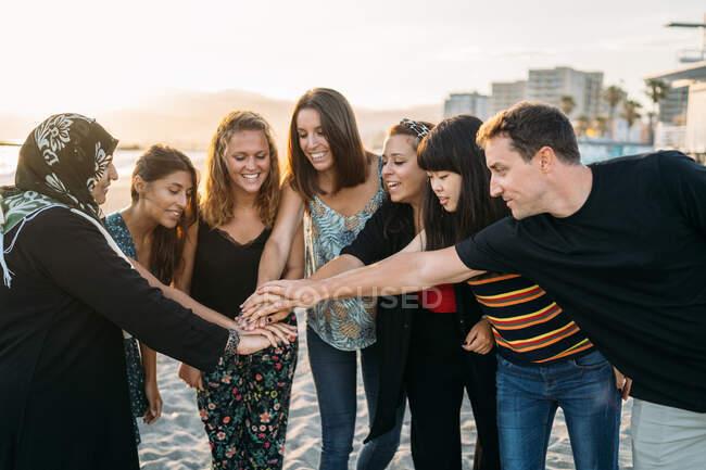 Eine Gruppe von Freunden schließt sich den Händen und plaudert am Strand mit der Sonne im Hintergrund — Stockfoto